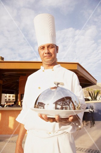 Hispanic male chef holding covered plate