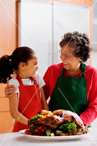 Hispanic grandmother and granddaughter laughing in kitchen