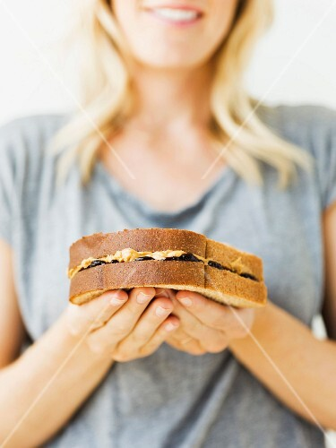 A young woman holding a peanut butter sandwich