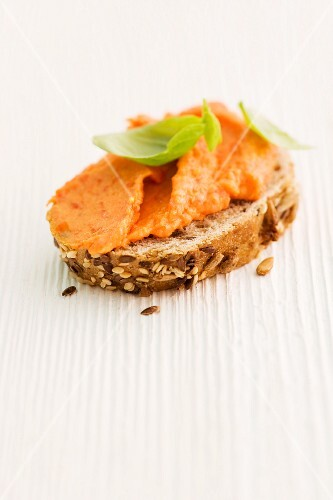 A slice of bread topped with red pepper & ricotta spread and basil