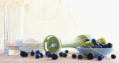 Still life featuring blueberries, kiwi and kitchen utensils
