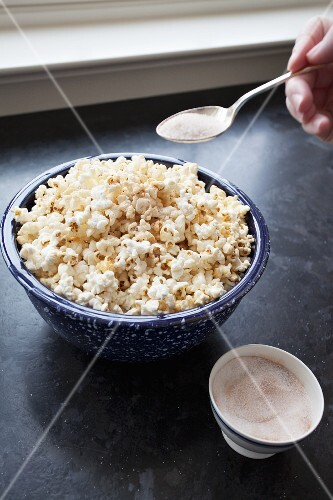Home-made popcorn being sprinkled with sugar