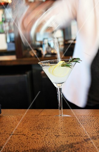 Lemon rosemary martini being poured