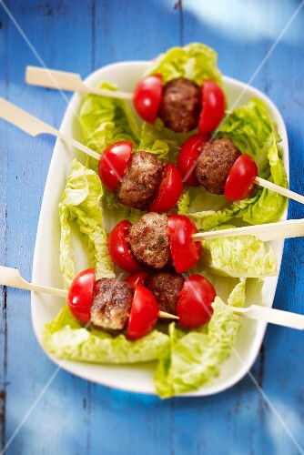 Meatball skewers with tomatoes on lettuce leaves