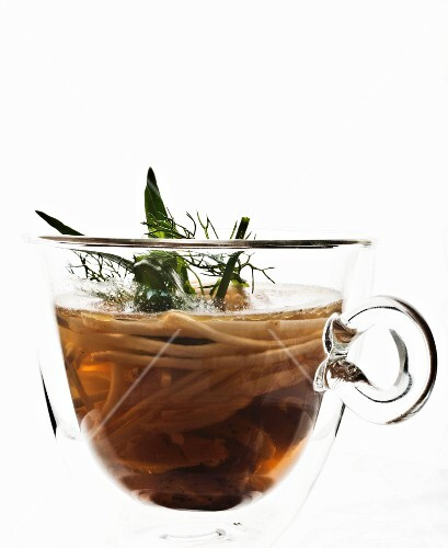 Chicken broth with celeriac in a glass cup against a white background