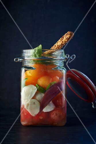 A jar filled with duck, melon, tomatoes and mozzarella