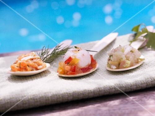 Assorted fish tartare on tasting spoons