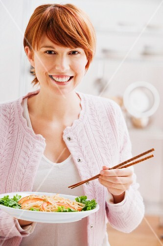 Woman eating with chopsticks