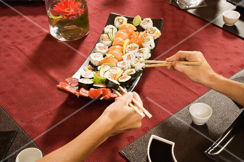 Hands with chopsticks taking sushi from plate