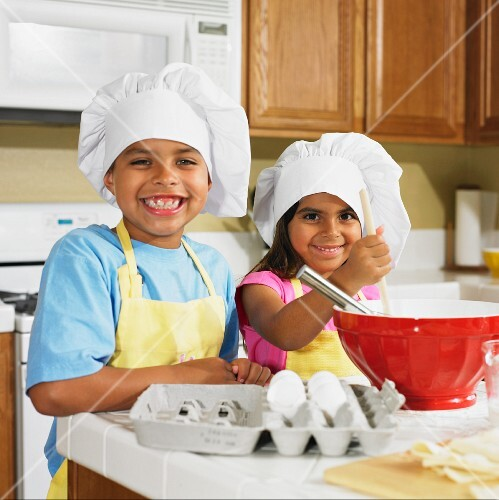 Hispanic brother and sister baking in kitchen