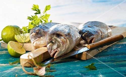 Three gilt-head bream on a wooden board with limes and herbs