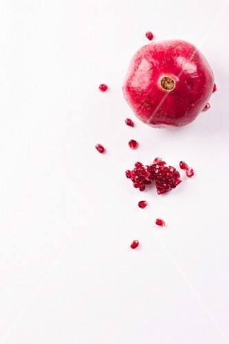 A whole pomegranate, pomegranate seeds and chunks of pomegranate