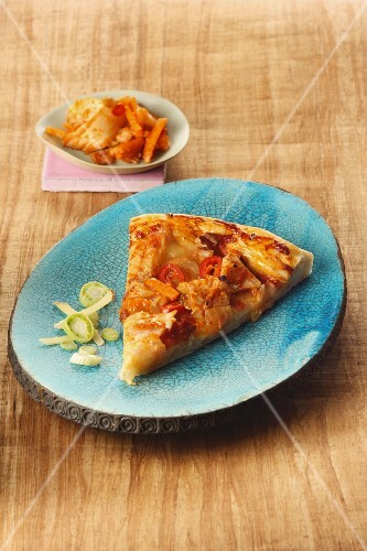 Pizza topped with kimchi, carrots and spring onions
