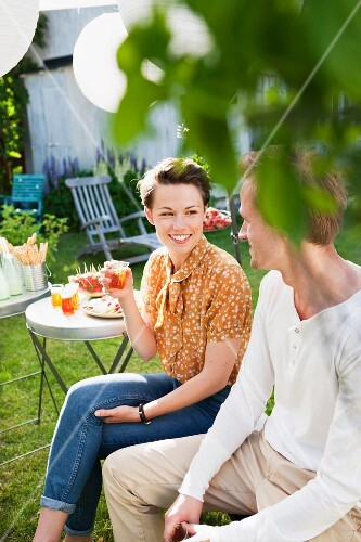 A man and a woman talking at a summer garden party