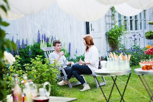 A young couple talking at a summer garden party