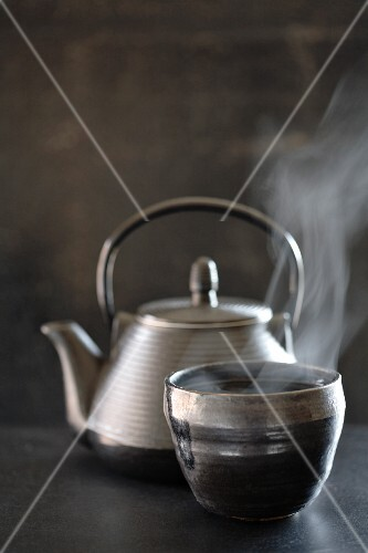 Tea pot and steaming cup of tea