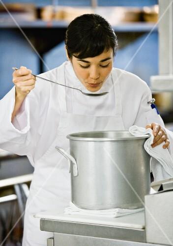 Asian female chef tasting food