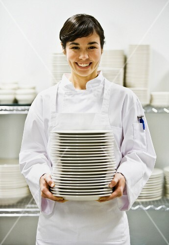 Asian female chef holding stack of plates
