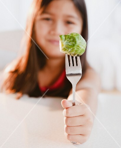 Mixed race girl holding brussels sprout