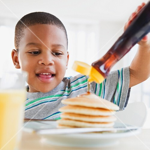 African American boy pouring syrup on pancakes