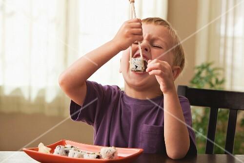 Caucasian boy eating sushi