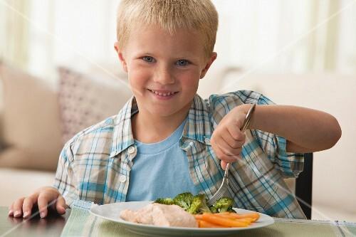 Caucasian boy eating dinner
