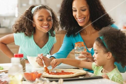 Mixed race family making pizza