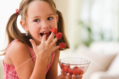 Girl eating raspberries from fingers