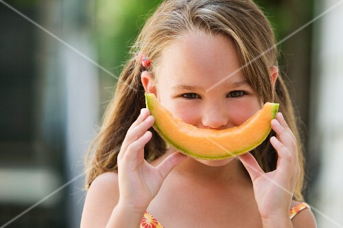 Girl holding a wedge of cantaloupe