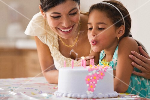 Mother watching daughter blow out birthday candles