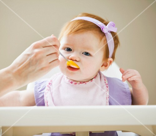 baby being fed looking at viewer