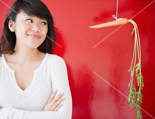 Asiatische Frau steht neben aufgehängter Karotte