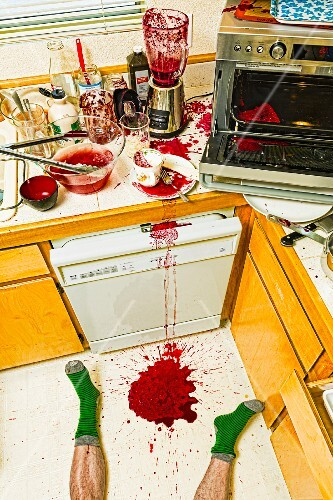 Man laying on floor in messy kitchen