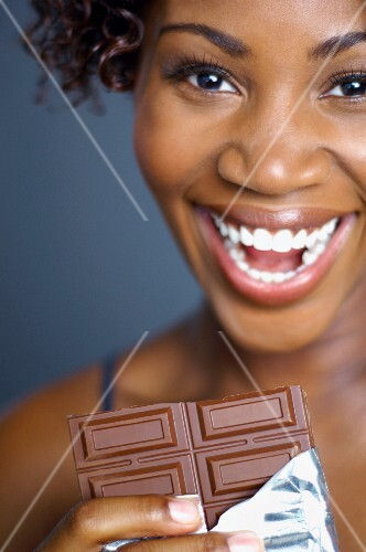 African woman eating chocolate bar