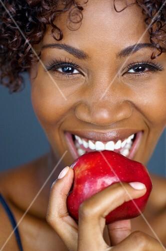 Dunkelhäutige Frau beisst in roten Apfel