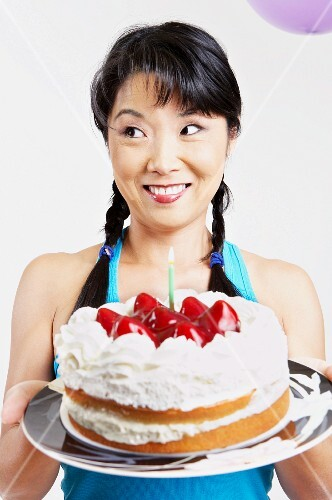 Asian woman holding cake with candle