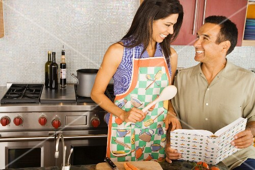 Hispanic couple reading cook book in kitchen