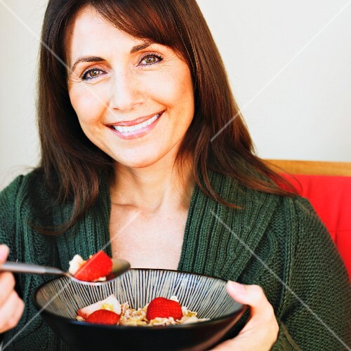 Hispanic woman eating cereal and fruit
