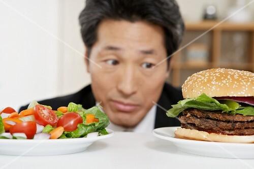Asian man looking at salad and hamburger