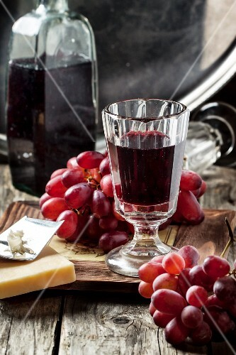 Vintage glass of red wine with bnch of red grapes and cheese