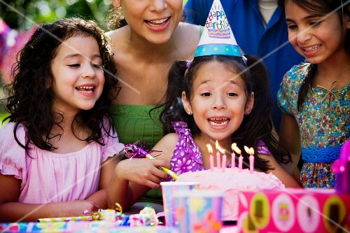 Hispanic girl blowing out candles at outdoor birthday party