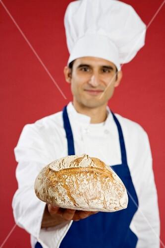 Hispanic chef holding fresh baked bread