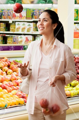 Mixed race woman tossing apple in supermarket
