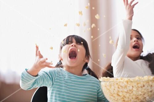 Playful girls throwing popcorn