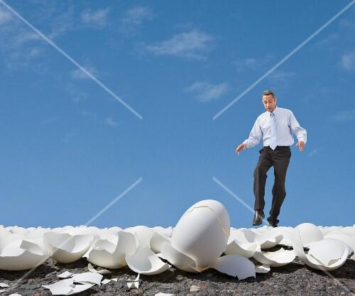 Mixed Race businessman walking on egg shells
