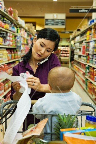 Asian woman reading list in grocery store
