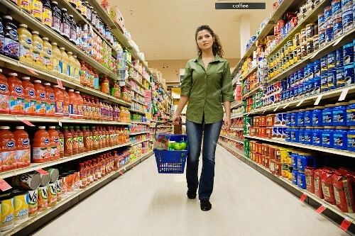 Hispanic woman carrying basket in grocery store