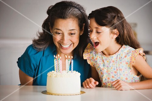 Hispanic grandmother and granddaughter with birthday cake