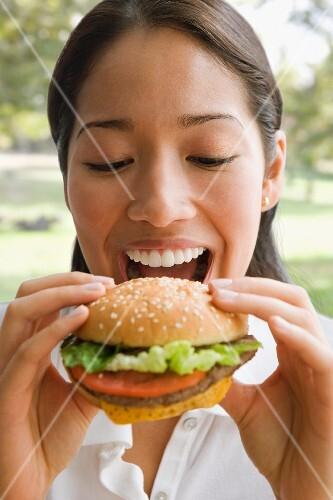 Asian woman eating hamburger