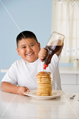 Hispanic boy pouring syrup on pancakes
